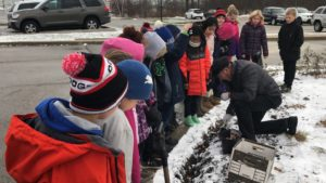 Grade 4 students planting flower bulbs with Mr. Paas.