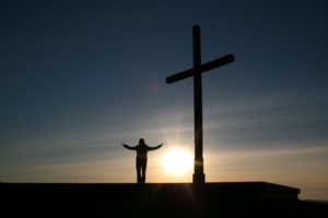 sunset and person beside cross